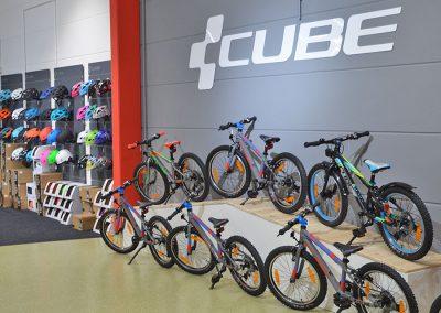 Ausstellerfläche mit CUBE Kinderfahrrädern verschiedene Modelle und Farben sowie Fahrradhelmen im Cube Store Zella-Mehlis